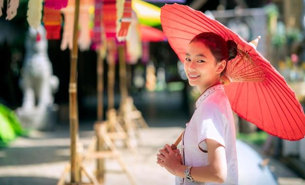 Azjatycka dziewczyna w północnym tradycyjnym kostiumu i czerwony parasol stoją w świątyni