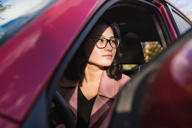 Azjatycka dziewczyna w samochodzie. dziewczyna odwraca wzrok.
