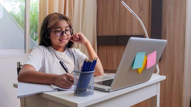 Azjatycka dziewczyna w słuchawkach siedzi przy biurku studiuje online na laptopie dziecko nosi zestaw słuchawkowy nauka za pomocą lekcji internetowych na kwarantannie student uczy się wirtualnego internetu online klasa ze szkoły z powodu covid19