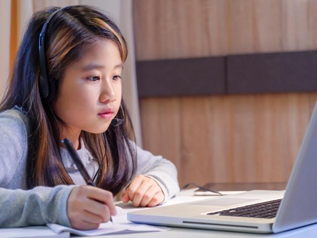 Azjatycka dziewczyna w słuchawkach siedzi przy biurku, studiuje online na laptopie dziecko nosi zestaw słuchawkowy, pismo odręczne w notatniku