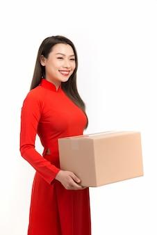 Azjatycka dziewczyna w tradycyjnym wietnamskim stroju trzymająca pudełko, życzenia księżycowego nowego roku