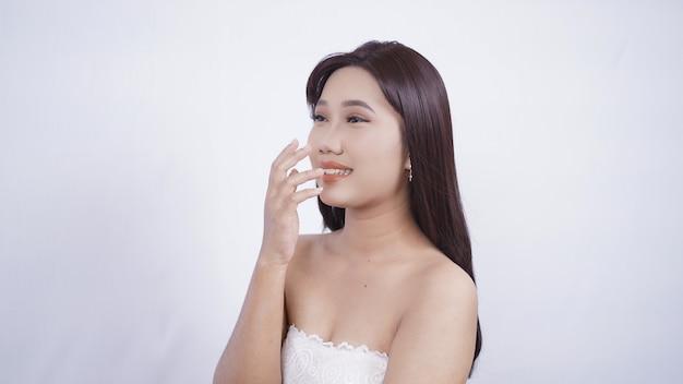 Azjatycka dziewczyna z chichoczącą ręką makijażem zakrywającym usta na białym tle