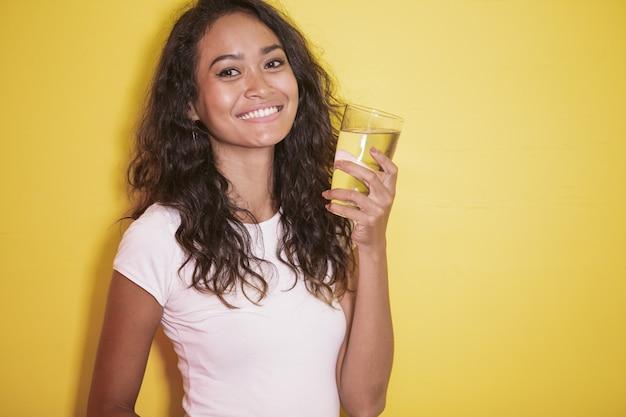 Azjatycka dziewczyna z pięknym uśmiechem i mieniem szkło woda