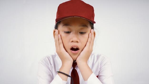 Azjatycka dziewczyna ze szkoły podstawowej, która jest zaskoczona tym, co widzi na białym tle