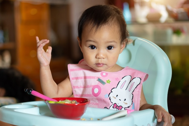Azjatycka dziewczynka 11 miesięcy je jedzenie na stole dla niemowląt.