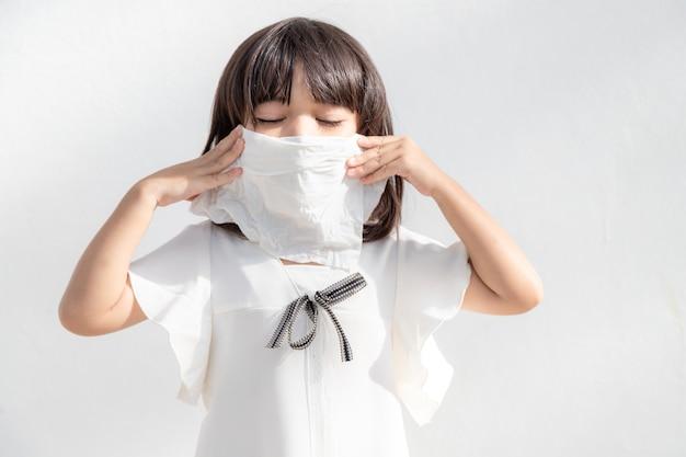 Azjatycka dziewczynka chora na kichanie w nos i zimny kaszel na bibułce