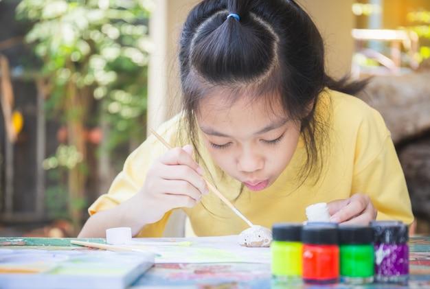 Azjatycka dziewczynka do kolorowania kamieni, twórcze dzieci z rockiem, kreatywne koncepcje dla dzieci