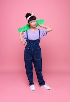 Azjatycka dziewczynka gospodarstwa deskorolka na różowej ścianie.