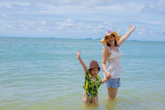 Azjatycka dziewczynka i matka podczas wakacji na plaży