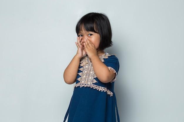 Azjatycka dziewczynka krzyczy i krzyczy ogłaszając na białym tle