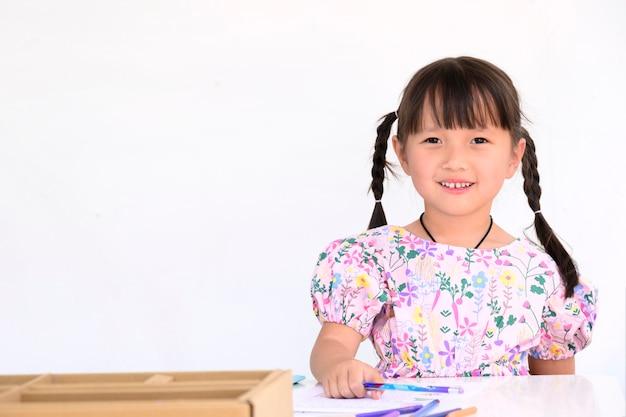 Azjatycka dziewczynka leży, rysunek lub odrabiany w papierowej książce dla dzieci w wieku przedszkolnym w domu biała ściana