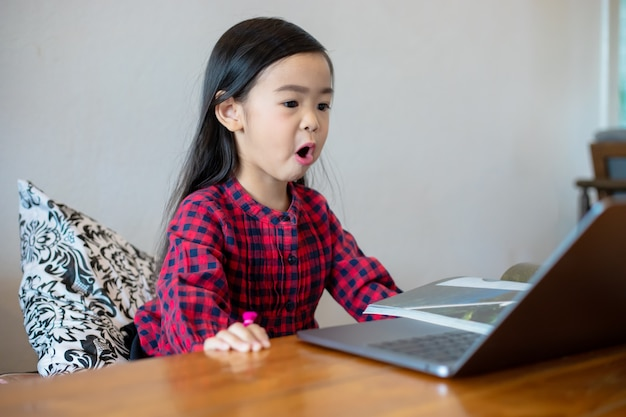 Azjatycka dziewczynka lub córki używają zeszytów i technologii do nauki online podczas wakacji szkolnych i oglądania kreskówek w domu. koncepcje edukacyjne i działania rodziny