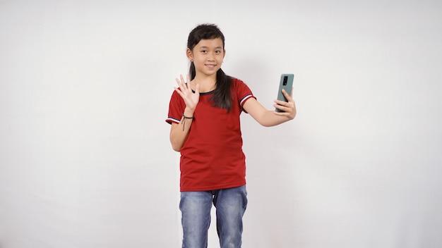 Azjatycka dziewczynka macha ręką trzymającą smartfona na białym tle