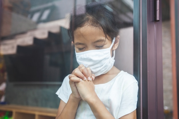Azjatycka dziewczynka nosząca maskę ochronną, modląca się o nową wolność dnia koronawirusa covid-19 i pozostania w domu poddana kwarantannie od koronawirusa covid-19 i zanieczyszczenia powietrza pm2.5.