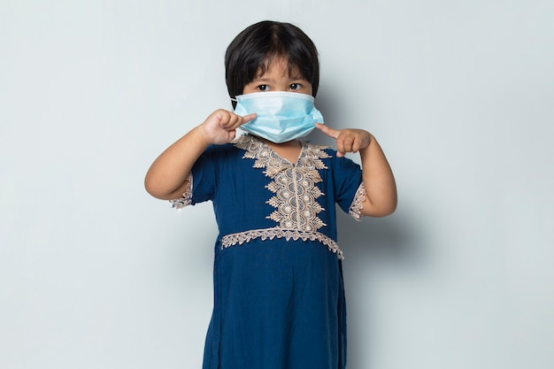Azjatycka dziewczynka nosząca medyczną maskę do ochrony przed wirusem koronowym na białym tle