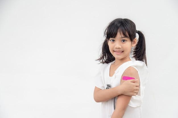 Azjatycka dziewczynka pokazując ramię po zaszczepieniu lub zaszczepieniu, szczepienia dzieci, koncepcja szczepionki covid delta