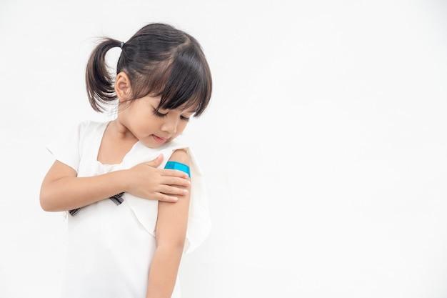 Azjatycka dziewczynka pokazująca ramię po zaszczepieniu lub szczepieniu dziecka