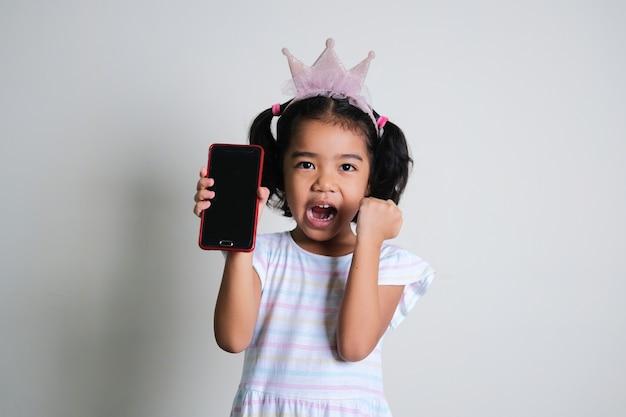 Azjatycka dziewczynka robi podekscytowany wyraz, pokazując pusty ekran telefonu komórkowego