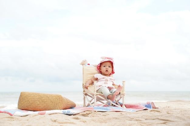 Azjatycka dziewczynka siedzi na krześle plaży.