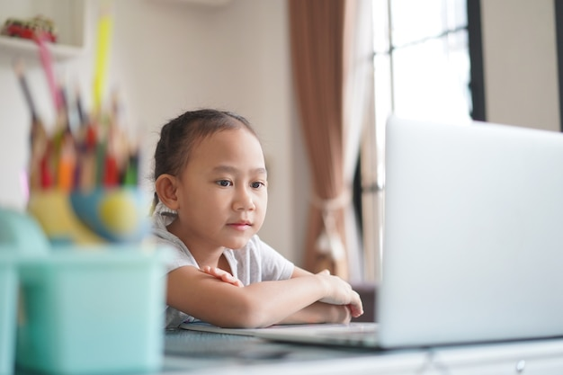 Azjatycka dziewczynka studiuje lekcję online odrabiania lekcji, edukacja na odległość społeczna online w koncepcji pomysłu w domu
