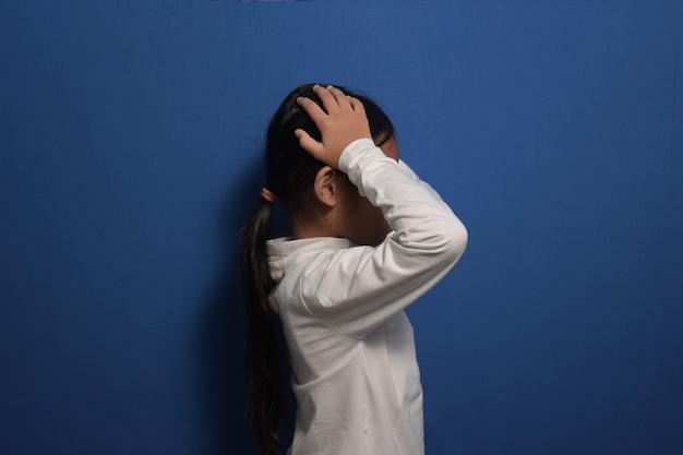 Azjatycka dziewczynka ubrana w białą koszulkę, patrząc na bok z rękami na głowie, ponieważ ból głowy
