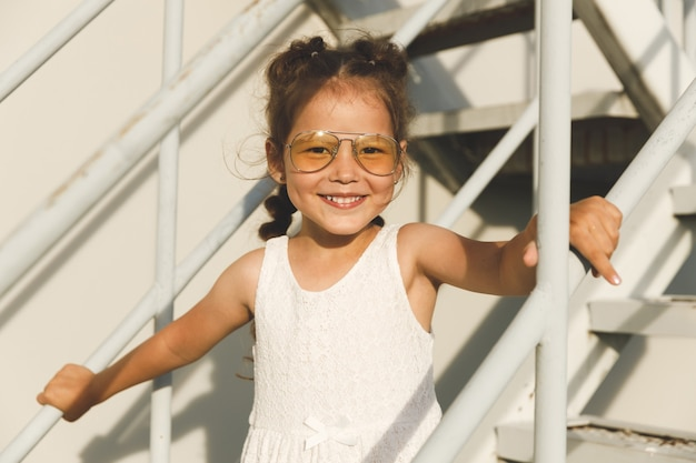 Azjatycka dziewczynka w białej sukni i okularach przeciwsłonecznych na białych schodach
