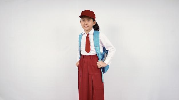 Azjatycka dziewczynka w kapeluszu i tornistrze uśmiecha się szczęśliwie na białym tle na białym tle