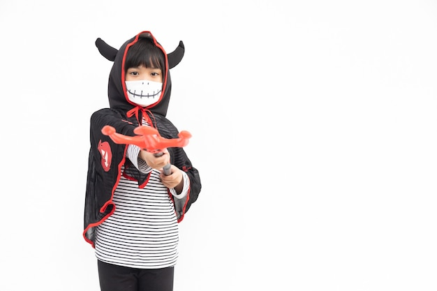 Azjatycka dziewczynka w kostiumie na halloween w masce medycznej. halloween ze środkami bezpieczeństwa od covid-19