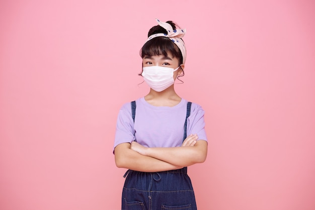 Azjatycka dziewczynka w masce, aby chronić ją przed wirusem covid-19 na różowej ścianie.