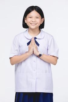 Azjatycka dziewczynka w mundurze studenckim, działająca na piłą oznacza hello.