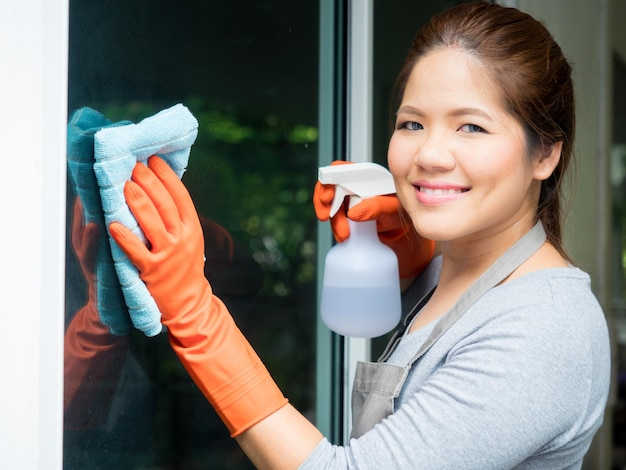 Azjatycka gospodyni domowa czyszczenie szyby okiennej