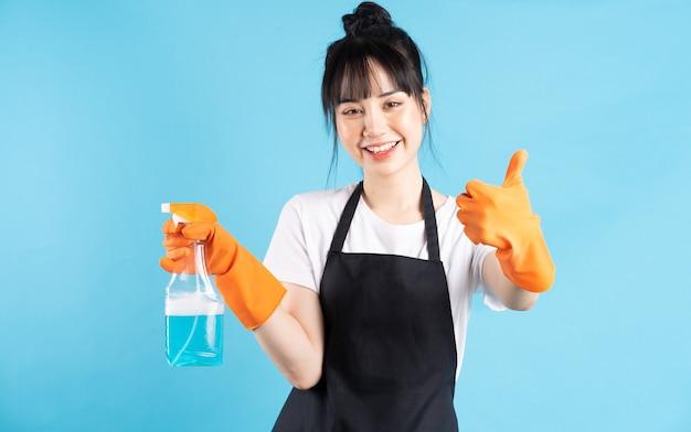Azjatycka gospodyni domowa ma na sobie pomarańczowe rękawiczki i trzyma w dłoni spray z wodą