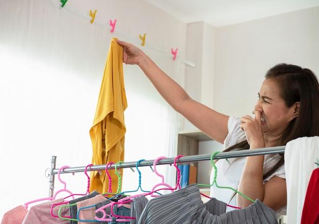Azjatycka gospodyni domowa śmierdzi śmierdzącą od ubrań