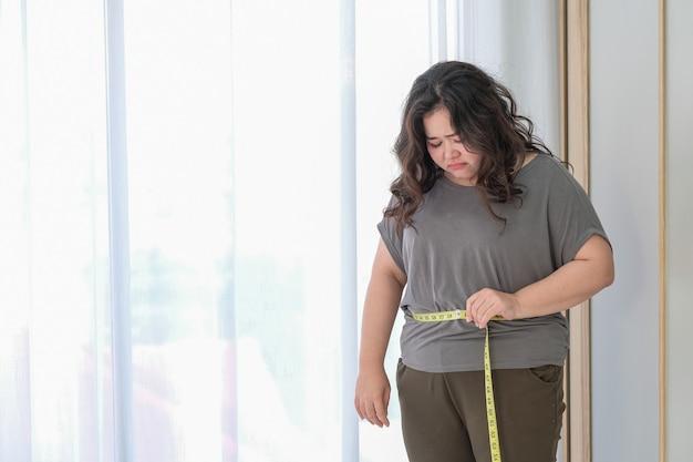 Azjatycka gruba kobieta jest smutna z powodu wzrostu rozmiaru po sprawdzeniu za pomocą taśmy mierniczej.