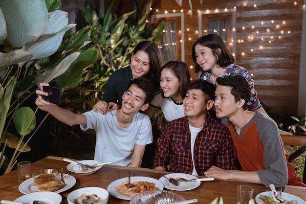 Azjatycka grupa bestfriend robi selfie ze smartfonem podczas imprezy w ogrodzie