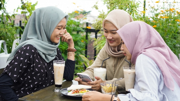 Azjatycka grupa hidżabu kobieta smilling w kawiarni z przyjacielem