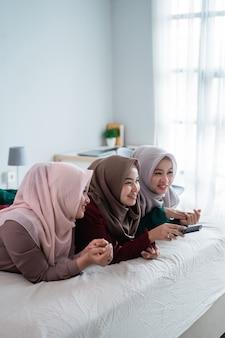 Azjatycka hidżab kobieta z przyjaciółmi leżącymi na łóżku cieszyć się oglądaniem telewizji