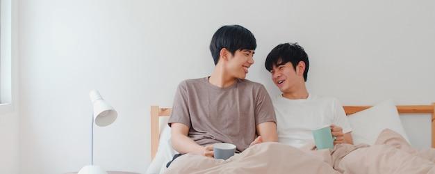 Azjatycka homoseksualista para opowiada mieć świetnego czas w nowożytnym domu. młody kochanek azji lgbtq + mężczyzna szczęśliwy zrelaksuj się wypij kawę po przebudzeniu, leżąc na łóżku w sypialni w domu rano.