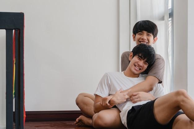 Azjatycka homoseksualna para kłama i ściska na podłoga w domu. młodzi azjaci lgbtq + mężczyźni całujący szczęśliwy relaks odpoczywają razem spędzają romantyczny czas w salonie z tęczową flagą w nowoczesnym domu rano.