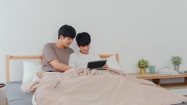 Azjatycka homoseksualna para używa pastylkę w domu. młodzi azjaci lgbtq + mężczyźni z radością odpoczywają razem po przebudzeniu, sprawdzają pocztę i media społecznościowe rano na łóżku w sypialni w domu.