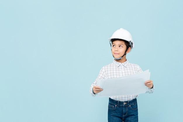 Azjatycka inżynier chłopiec jest ubranym hardhat i trzyma projekt