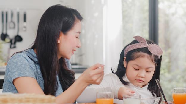 Azjatycka japońska rodzina ma śniadanie w domu. azjatycka mama i córka szczęśliwi opowiadamy wpólnie podczas gdy jedzący chleb, pije sok pomarańczowego, płatków kukurydzanych zboże i mleko na stole w nowożytnej kuchni w ranku.