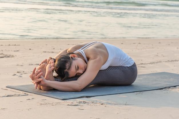 Azjatycka joga kobieta robi ćwiczeniu na plaży.