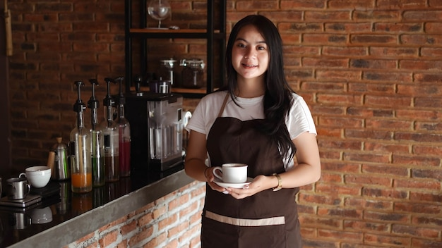 Azjatycka kobieta barista uśmiecha się w ladzie kawiarni. kobieta barista trzymając filiżankę kawy w kawiarni