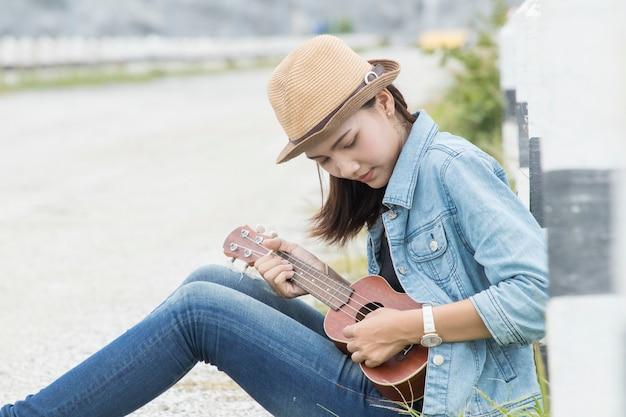 Azjatycka kobieta bawić się ukulele gitarę przy plenerowym