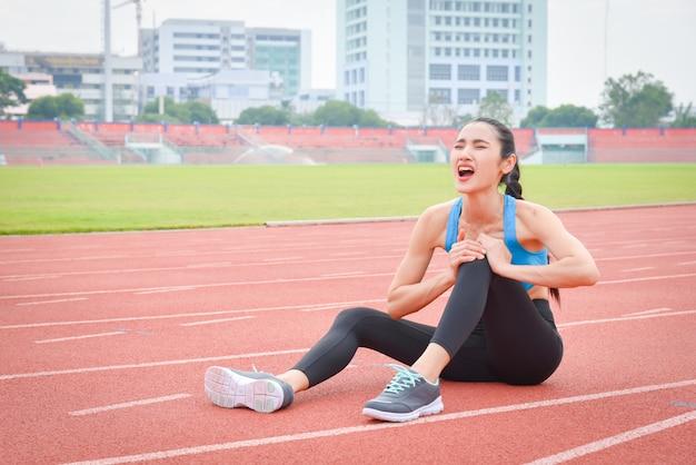 Azjatycka kobieta biegacz siedzi na bieżni, cierpi na ból w nodze po uruchomieniu na świeżym powietrzu.
