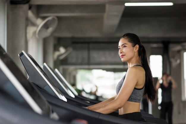 Azjatycka kobieta biegająca na karuzeli w gym