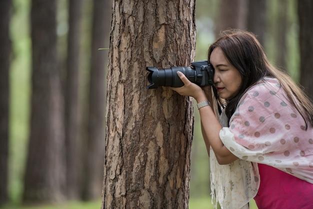 Azjatycka kobieta bierze fotografię z dslr, strzela pozę z drzewnym pojęciem.