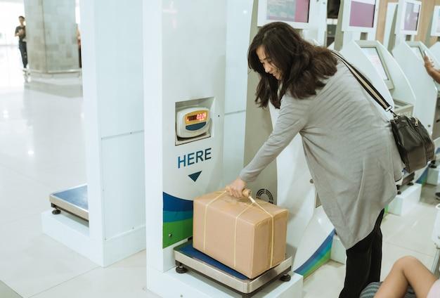 Azjatycka kobieta bierze karton na skala bagażu