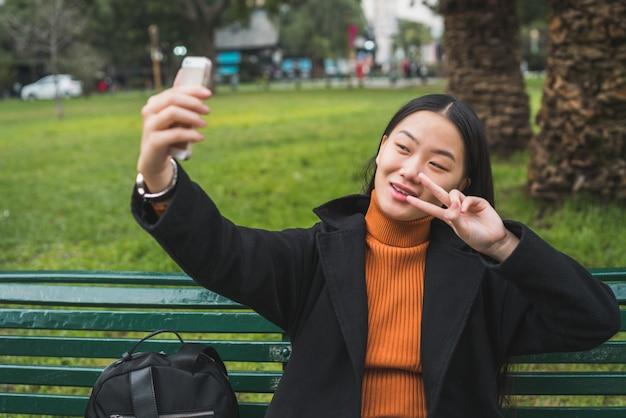 Azjatycka kobieta bierze selfie z telefonem.